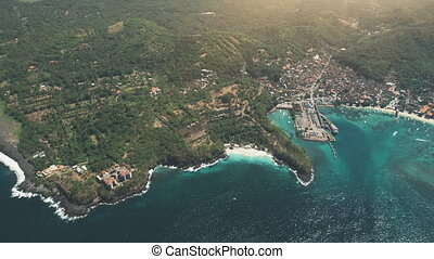 Aerial Drone Top View of Tropical Island, Crystal Ocean, Harbour Port and Green Forest Mountains. Travel Vacation Paradise Tourism Concept. Exotic Nature Landscape. Bali Island, Indonesia. Zoom out 4K