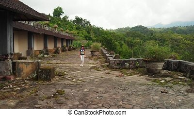 Aerial drone video of woman in abandoned hotel in Bedugul, Bali island.