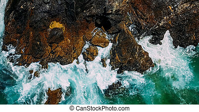 Aerial Drone View Of Dramatic Ocean Waves Crushing On Rocky Landscape