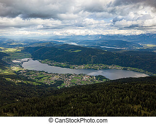 Aerial drone view on Ossiacher Lake in Carinthia, Austria on a summer day with great cloudscape and Lake Woerthersee in the background