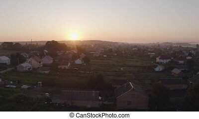Aerial drone descent over old village at sunrise. Swallows birds fly in large swarms. Aerial camera bird eye view. Unsurpassed view of the sun which illuminates the whole landscape.
