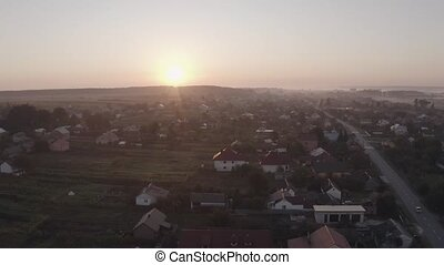 Aerial drone descent over old village at sunrise. Swallows birds are flying. Aerial camera bird eye view. Unsurpassed view of the sun which illuminates the whole landscape.