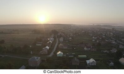 Aerial drone descent over old village at sunrise. Aerial camera bird eye view. Unsurpassed view of the sun which illuminates the whole landscape. Thick fog covered all the fields