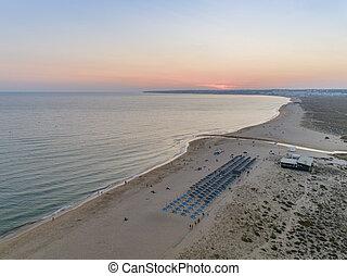 Aerial dusk seascape of Salgados beach in Albufeira, Algarve.