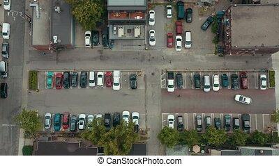 Aerial establishing shot of a parking lot a big city. Cinematic 4K footage.