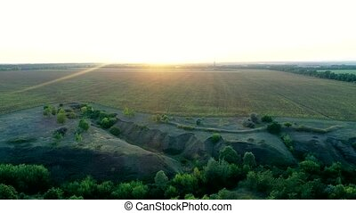 Aerial evening sunshine view of spacious field near the...