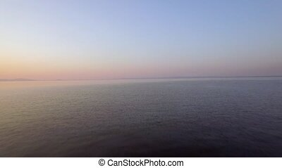 Aerial evening view of vast sea, lonely boat and skyline