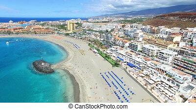 Aerial flight above beautiful beach and ocean in Adeje Playa...