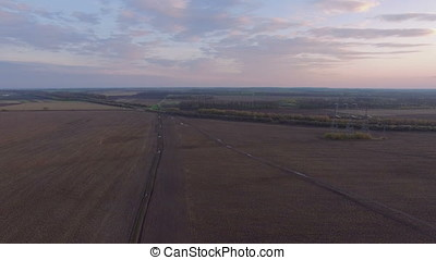 Aerial flight above rural path at High voltage power line