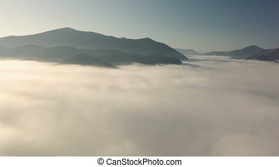 Aerial flight into the clouds in morning mountains landscape