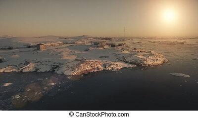 Aerial flight over Antarctic base. Sunset view. - Antarctica...
