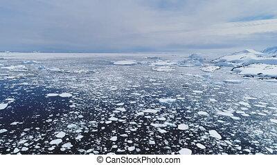 Aerial flight over Antarctica ice frozen ocean.