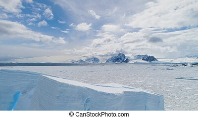 Aerial flight over Antarctica iceberg, ocean.