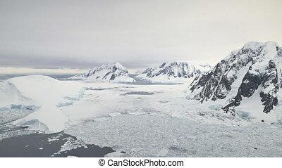 Aerial flight over Antarctica mountains, ocean.