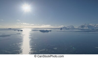Aerial flight over Antarctica ocean. Bright sun.