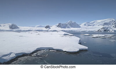 Aerial flight over Antarctica shoreline, ocean.