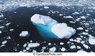 Aerial flight over iceberg among Antarctica ocean.