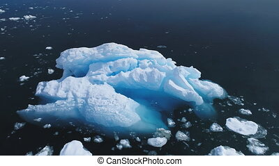 Aerial flight over iceberg in Antarctica ocean.