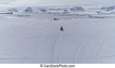 Aerial flight over moving snowmobile. Antarctica.