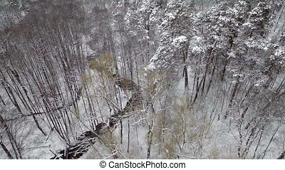 AERIAL: Flight over the river in winter. Falling snow