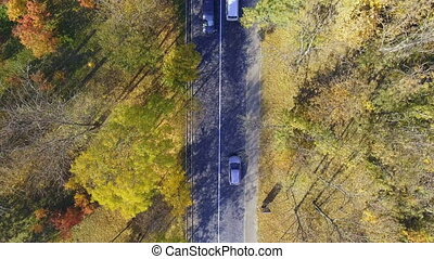 Overhead aerial top view over car travelling through...