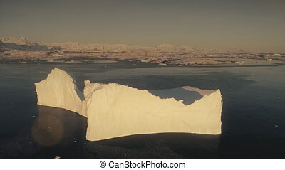 Aerial flight over the sunlit iceberg. Antarctica. -...