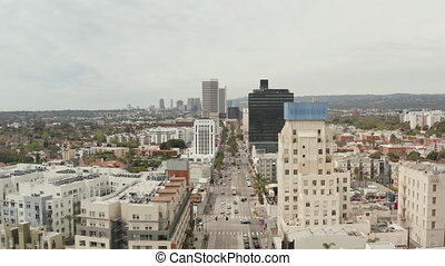 AERIAL: Flight over Wilshire Boulevard close to Street and Buildings with Car Traffic in Los Angeles, California on Overcast Day