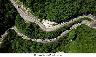 Aerial fly over a curved winding road trough the mountains with cars and truck