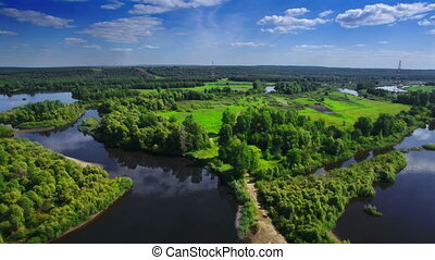 AERIAL Fly over clear blue river and green native forest in...