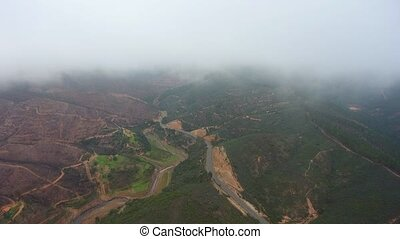 Aerial. Flying drone in fog and clouds over the hills in Monchique Portugal.