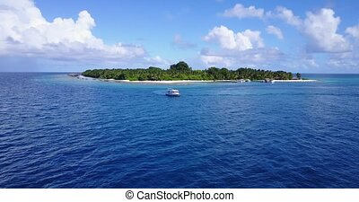 Aerial flying drone view of Maldives white sandy beach on sunny tropical paradise island with aqua blue sky sea water ocean 4k boat sailing