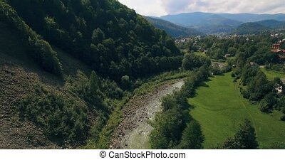 Flying low above the river carving its way through the spring valley. 4k