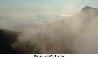flying over a mountain range in a fog in autumn