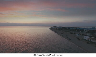 Aerial Flying over the beach at sunset