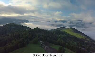 Aerial foggy country landscape in morning light above clouds with beautiful colors at sunrise