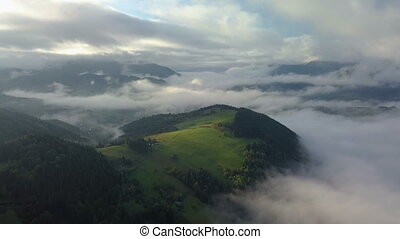 Aerial foggy country landscape in morning light above clouds with beautiful colors at sunrise. Pan left to right