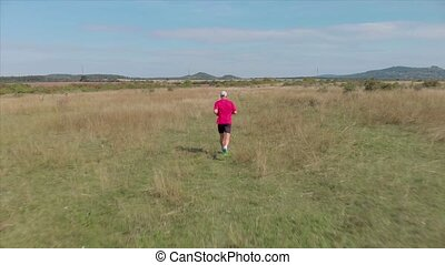 Aerial footage from a man running on the Hungarian meadow