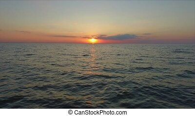 Aerial footage Ocean fly over at sunset, just above the ocean waves facing the sun