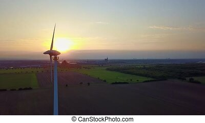 Aerial footage of a wind turbine in front of the setting sun Wind Power - circling around wind turbine