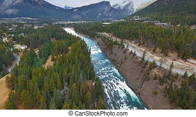 Aerial footage of Bow River flowing with wooded banks in Banff, Alberta, Canada