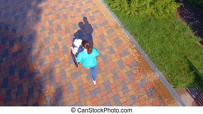 Aerial footage of caregiver walking with disabled senior in wheelchair