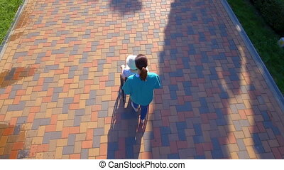 Aerial footage of caregiver walking with disabled senior in...