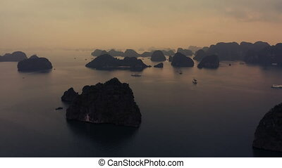 Aerial footage of Ha Long Bay Junk boats and cruise ships in the bay at Sunrise