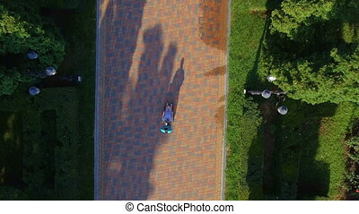 Aerial footage of nurse pushing elderly woman on wheelchair