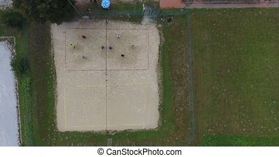 Aerial footage of people playing beach volleyball.