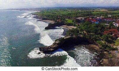 Aerial footage of sea coast near to Tanahlot temple on the Bali Island