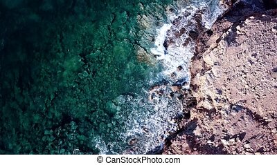 Aerial footage of surge of waves at a rocky coast with clear...
