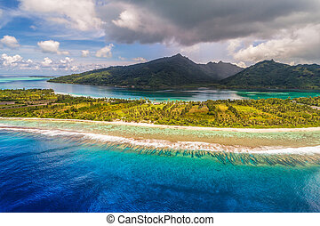 Aerial French Polynesia luxury travel honeymoon destination. Beach vacation at motu island of Huahine, Tahiti, Oceania adventure. View from above of paradise, French Polynesia, South Pacific Ocean.