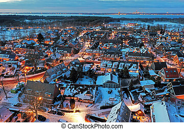 Aerial from a snowy village Huizen in winter in the Netherlands at twilight