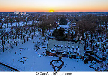 Aerial from a traditional dutch landscape in winter at sunset in the Netherlands